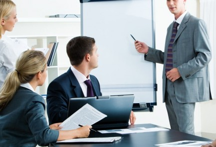 Image of smart business people looking at their leader while he explaining something on whiteboard during seminar